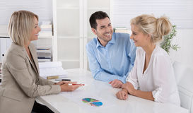 Young couple customers and adviser or agent talking about financ. Young married couple sitting with an adviser at desk in a guidance or professional business Royalty Free Stock Photography