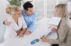 Young couple customers and adviser or agent talking about financ. Young married couple sitting with an adviser at desk in a guidance or professional business Stock Images
