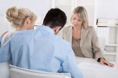 Young couple customers and adviser or agent talking about financ. Young married couple sitting with an adviser at desk in a guidance or professional business Royalty Free Stock Photo