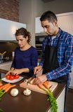 Young couple cutting vegetables in the kitchen Stock Images