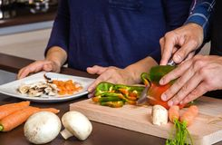 Young couple cutting vegetables in the kitchen Stock Photo