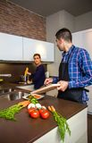 Young couple cutting vegetables in the kitchen Stock Image