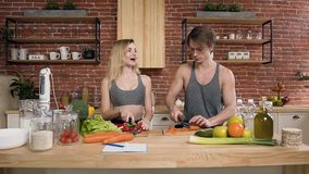 Young couple is cutting vegetables on wooden board for cooking the salad in the kitchen at home. Healthy food and stock footage