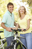 Young Couple On Cycle Ride in Park Royalty Free Stock Photography