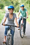 Young Couple Cycling Along Country Road Stock Photography