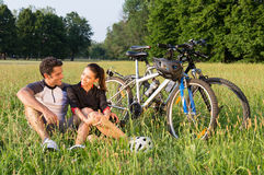 Young Couple Cycling In Meadow Stock Images