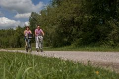 Young couple cycling with modern small e-bikes royalty free stock images