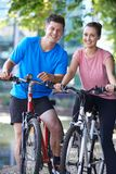 Portrait Of Young Couple Cycling Next To River In Urban Setting royalty free stock photos