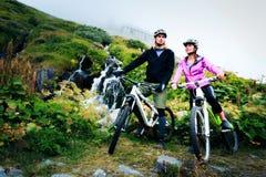Young Couple Cycling. Shot taken in Switzerland, near Rhone Glacier and Furka Pass Stock Photo