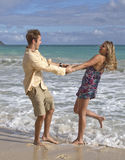 A young couple dance on the beach Stock Photography