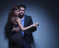 Young couple in dance pose. Portrait of a young fashion couple dancing while the men is looking into the camera and the women smiles away. on a dark blue Stock Photos