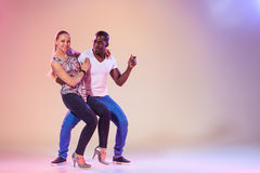 Young couple dances social Caribbean Salsa, studio shot Royalty Free Stock Images