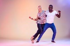 Young couple dances social Caribbean Salsa, studio shot Stock Photography