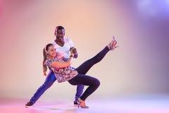 Young couple dances social Caribbean Salsa, studio shot Stock Images