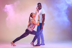 Young couple dances social Caribbean Salsa, studio shot Stock Photos