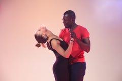 Young couple dances social Caribbean Salsa, studio shot Royalty Free Stock Photography