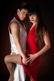 Young couple dancing embrace passion romance. On dark red light background Stock Photo