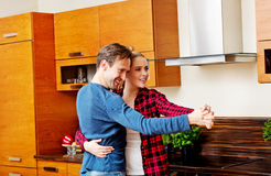 Young couple dancing and having fun in the kitchen Stock Photos