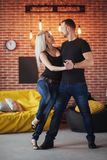 Young couple dancing latin music: Bachata, merengue, salsa. Two elegance pose on cafe with brick walls.  royalty free stock photography
