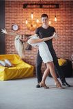 Young couple dancing latin music: Bachata, merengue, salsa. Two elegance pose on cafe with brick walls Royalty Free Stock Photos