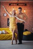 Young couple dancing latin music: Bachata, merengue, salsa. Two elegance pose on cafe with brick walls Royalty Free Stock Photography