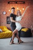 Young couple dancing latin music: Bachata, merengue, salsa. Two elegance pose on cafe with brick walls Stock Photo