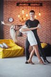 Young couple dancing latin music: Bachata, merengue, salsa. Two elegance pose on cafe with brick walls Stock Photos