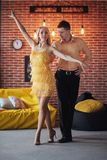 Young couple dancing latin music: Bachata, merengue, salsa. Two elegance pose on cafe with brick walls stock image