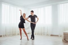 Young couple dancing latin music: Bachata, merengue, salsa. Two elegance pose on white room Stock Images