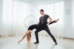Young couple dancing latin music: Bachata, merengue, salsa. Two elegance pose on white room Stock Image