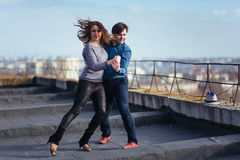 Young couple dancing on the roof of a tall building Stock Photography