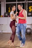 Young couple dancing social dance kizomba in big studio hall royalty free stock photography