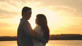 Young couple dancing at sunset on beach. Loving man and woman dance in bright rays of sun on the background of the lake stock video footage