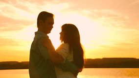 Young couple dancing at sunset on beach. Loving man and woman dance in bright rays of sun on the background of the lake stock video