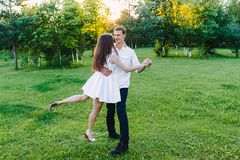 Young couple dancing sweetly on a grass royalty free stock photo