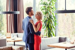 Young couple on date in restaurant dancing cheerful. Young men and women on date in restaurant hugging dancing smiling cheerful stock images
