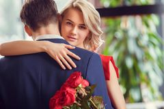 Young couple on date in restaurant dancing holding bouquet. Young men and women on date in restaurant dancing together holding bouquet of red roses royalty free stock photos