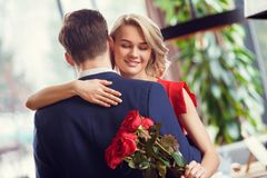 Young couple on date in restaurant dancing holding bouquet woman closed eyes joyful. Young men and women on date in restaurant dancing together holding bouquet royalty free stock image
