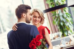 Young couple on date in restaurant dancing sensual holding bouquet. Young men and women on date in restaurant dancing sensual together holding bouquet of red stock photography
