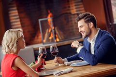 Young couple on date in restaurant sitting drinking wine talking joyful royalty free stock images