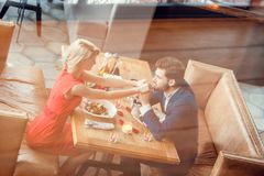Young couple on date in restaurant sitting eating salad man kissing woman`s hands joyful reflection top view royalty free stock image