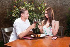 Young couple on date toasting with wine. Young couple on date outside on terrace toasting with wine looking at each other and having desert Stock Photography