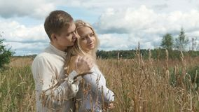 Young blond woman and her boyfriend are hugging on the field with wheat. Young couple on date in wheat field. The guy hugs his girlfriend and gently pats her on stock video footage