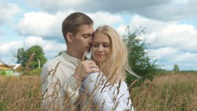 Young couple on date in wheat field. slow motion. Young couple on date in wheat field. The guy hugs his girlfriend and gently pats her on the shoulder. She stock footage