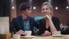 Young couple dating in café. A guy with a smartphone in his hand and a girl who is drinking coffee have a lively. Young couple dating in cafe. A guy with a stock footage