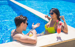 Young couple dating at the edge of the swimming pool Stock Images