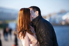 Young couple dating and kissing in the city park. Young happy couple in love dating outdoors in the evening kissing stock photo