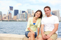 Young couple dating in New York. Portrait of multi-ethnic couple with Manhattan and New York City Skyline in background. Asian woman, Caucasian men tourists on Royalty Free Stock Photography