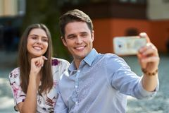 Young couple dating in the park and using smartphones. Picture of young couple dating in the park in summer royalty free stock photos