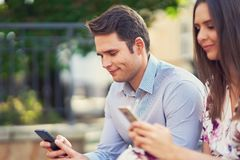 Young couple dating in the park and using smartphones. Picture of young couple dating in the park in summer stock photo